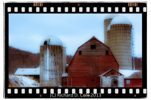 Red dairy barn with four silos in Rupert VT